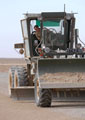 A Royal Engineer Grader works on the Temporary Landing Zone at Camp Bastion, Helmand, Afghanistan, 2006