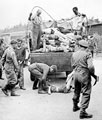 A British soldier guards SS members as they collect the dead at Belsen following its liberation, April 1945