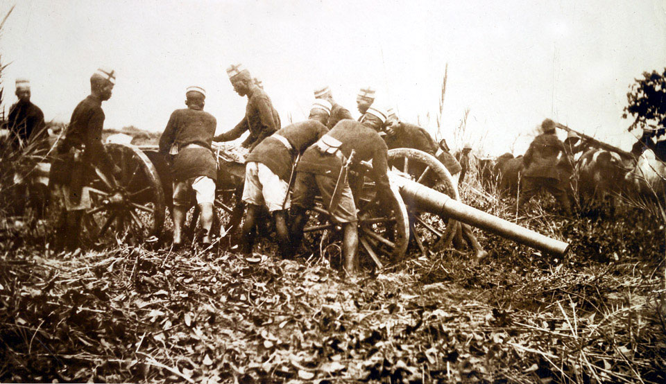 Askaris getting field gun into position, East Africa, 1914 (c)