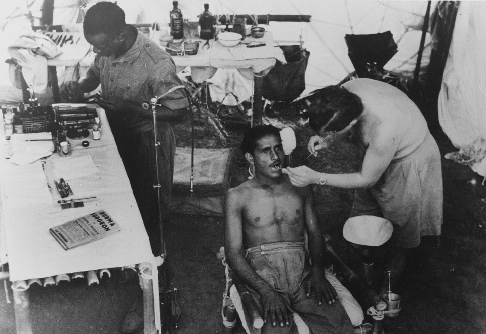A dentist at work in a make-shift surgery, Burma, 1944 (c)