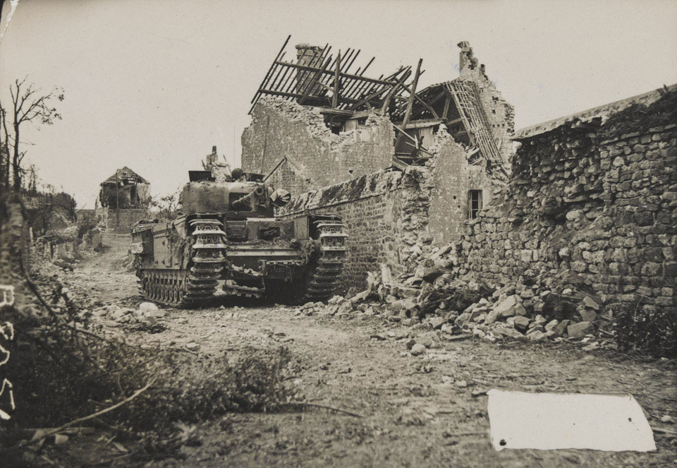 'A Churchill tank awaits possible enemy counter-attack in a ruined Normandy village', July 1944