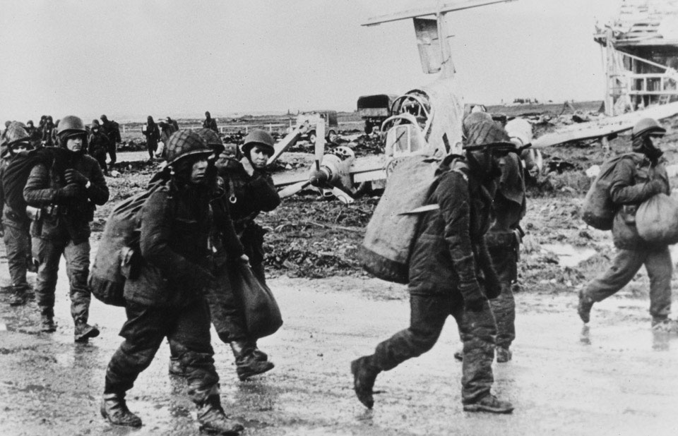 Argentine prisoners of war pass a wrecked Pucara ground attack aircraft, Goose Green, Falklands, 1982