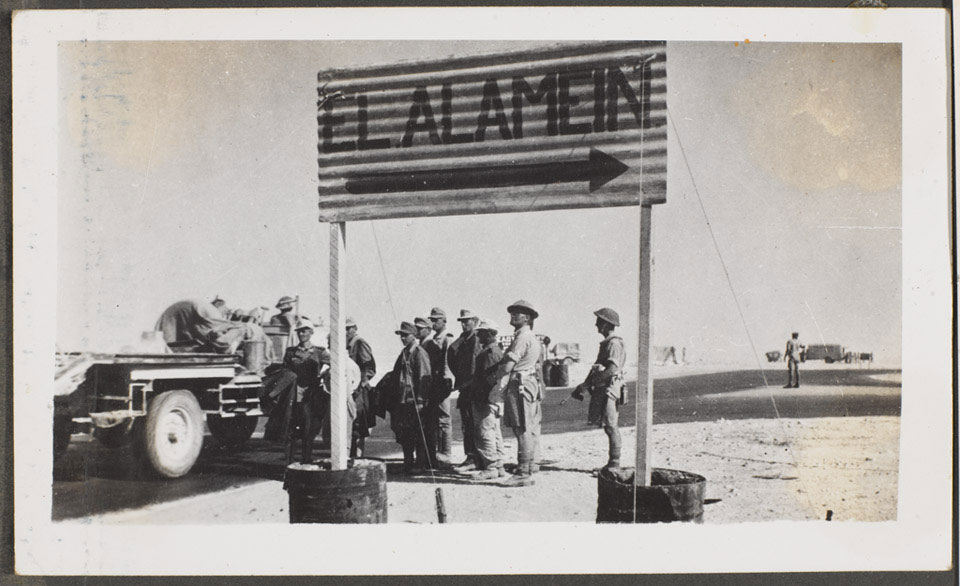 German prisoners of war under guard by a signpost to El Alamein, 1942