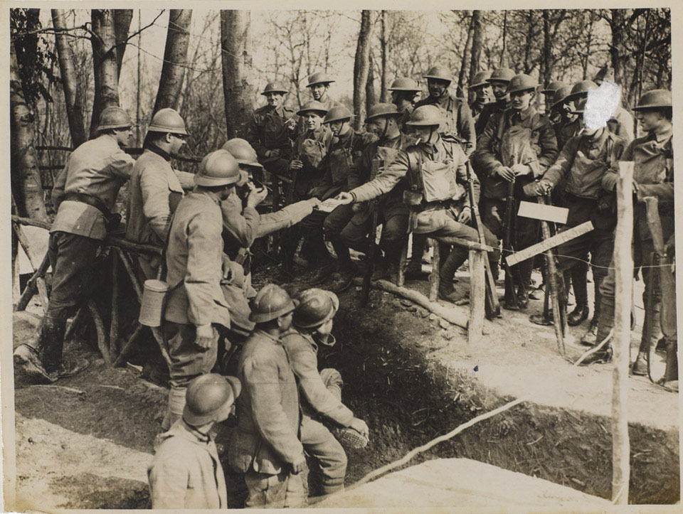 'On the right of the new line taken over from the French. British and French troops make friends outside a dug-out', 16 March 1918
