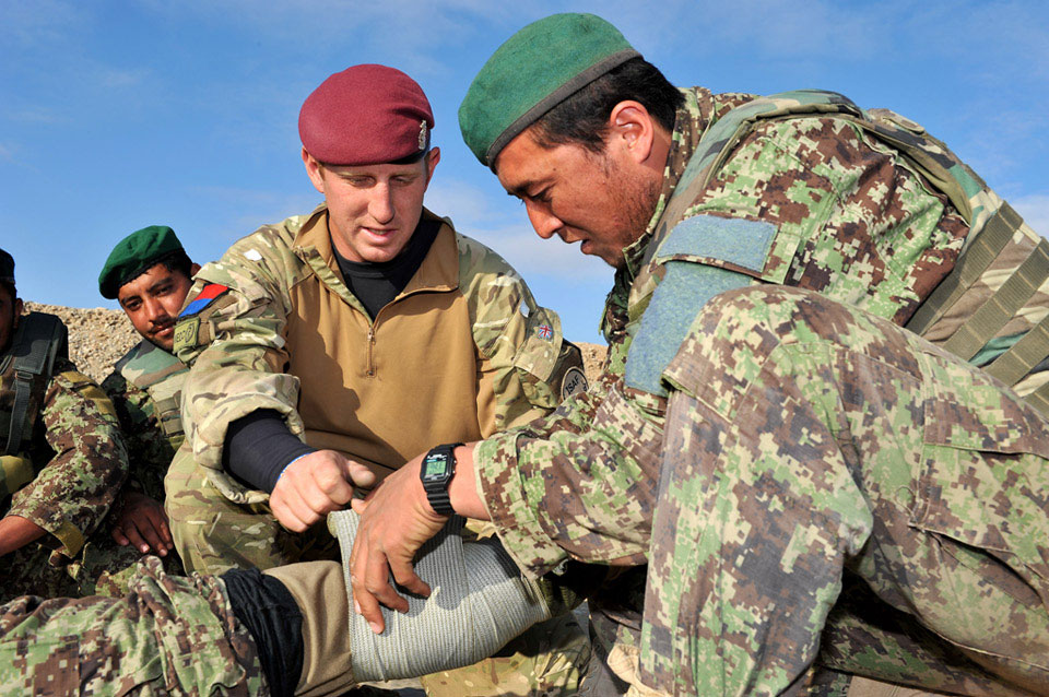 A corporal from the Royal Army Medical Corps trains a soldier of the Afghan National Army to apply a field dressing, near Gereshk, Helmand Province, January 2011.