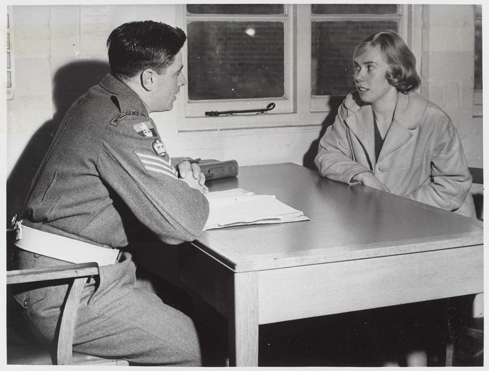 An Intelligence Corps staff sergeant questioning a civilian, 1960 (c)