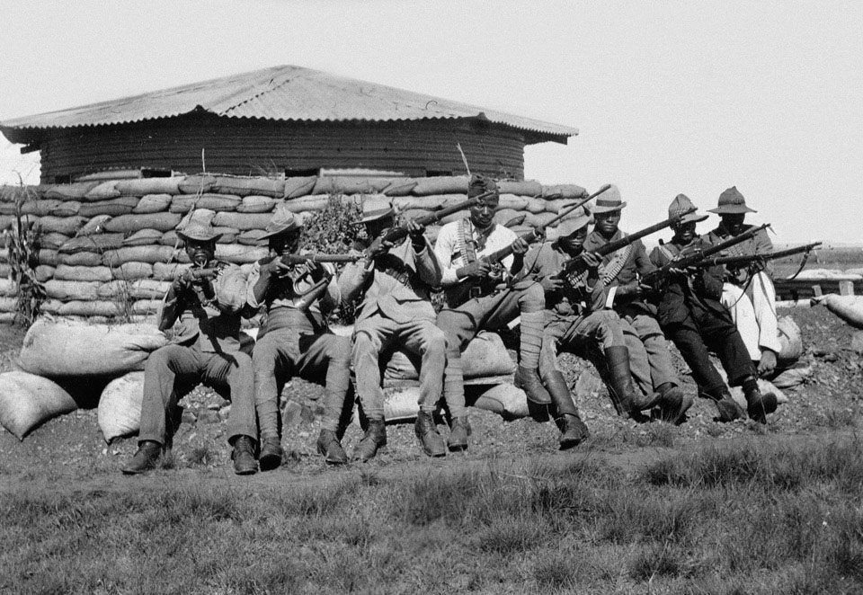 Black African soldiers seated outside a blockhouse, South Africa, 1900 (c)